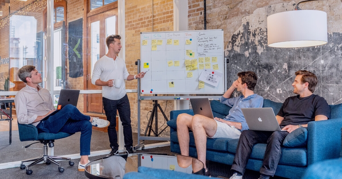 Four men in a meeting planning on a whiteboard