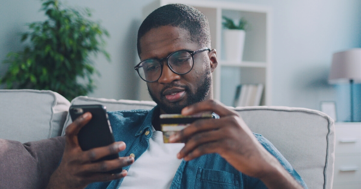 Man sitting on sofa using card to make online purchase on phone